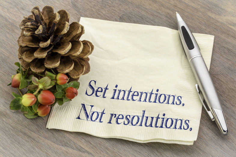 Set Intentions Not Resolutions New Year Goals Concept Handwriting On A Napkin With A Pine Cone